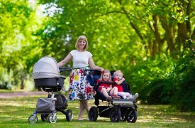 pic of mother baby nature  - Young mother walking in a park with children in pushchair - JPG
