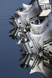 image of outboard engine  - Close up of four outboard boat motors and propellers - JPG