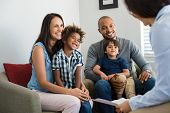 Happy young family sitting on couch and talking with family counselor. Smiling parents with adopted  poster