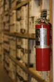 stock photo of fire extinguishers  - this fire extinguisher hangs in the records management warehouse as a safety measure to protect these documents from a fire outbreak - JPG