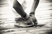 closeup of woman feet and hands in yoga postion lot of bracelets and rings outdoor shot on wooden po poster