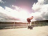 Постер, плакат: Roller Skater In Action Man Ride In Inline Skates Ride Along Promenade Handrail Sky In Background
