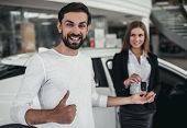 Salesperson With Customer In Car Dealership poster