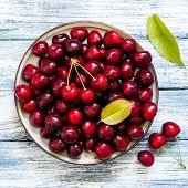 Fresh Cherry On Plate On Wooden Blue Background. Fresh Ripe Cherries. Sweet Cherries poster