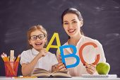 Back to school! Child is learning to write. Adult woman teaches child the alphabet. poster