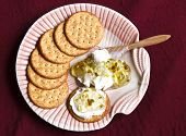 picture of spreader  - Cream cheese and crackers with jalepeno jelly and spreader on a shell shaped plate and on a red textile - JPG