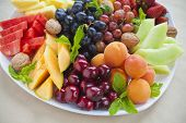 picture of fruit platter  - Colorful summer fruit platter with grapes pineapple watermelon cherries apricots strawberries cantaloupe walnuts and mint - JPG