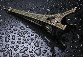 Statuette Of The Tower Of Eifel With Water Drops On A Black Background. poster
