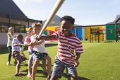 Front view of multi ethnic group of happy school kids playing tug of war in playground poster