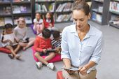 Overhead view of teacher looking down her tablet while school kids relaxing themselves on cushions i poster