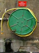 stock photo of firehose  - Fire hose wound around an old green drum - JPG
