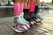 Row Of Kangoo Jumping Boots At Womens Legs. Group Of Girls At Fitness Workout poster