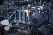 Car Mechanic With Wrench In Garage.workers Are Welding Auto Parts. poster