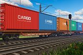 image of railroad yard  - Freight train with cargo containers passing by - JPG