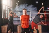 Having A Good Stretch. Focused Muscular Athletes In Sports Clothing Looking At Camera While Stretchi poster