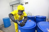 stock photo of toxic substance  - fully protected in yellow uniform - JPG