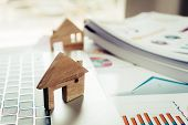 Property Real Estate Mortgage Loan Or Investment Concept: Wooden Home Model On Computer With Chart R poster