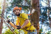 Young Male Man Adult Wears Protective Helmet With Action Camera Having Fun In Extreme Rope Park, Amu poster
