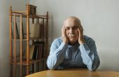Worried Elderly Man With His Head In His Hands Seated At A Table Indoor Staring Dejectedly Ahead Wit poster