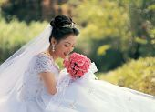 image of semi-formal  - Beautiful Asian bride in semi formal gown with bouquet of wild flowers - JPG