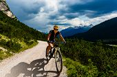 Woman cycling on electric bike on mountain trail. Woman riding on bike in Dolomites mountains landsc poster