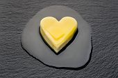 Heart-shaped Piece Of Butter Melting On Black Pan poster