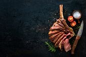 Grilled dry aged tomahawk steak sliced as close-up on dark background poster