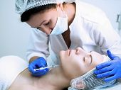 Beauty Injection. Cosmetician In Parlour With Head Of Patient And A Disposable Syringe In Hand. Clie poster