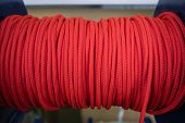 The Red Rope Is Reeled Up On The Coil In Shop. A Saving Or Safety Rope For Climbers. Texture Of A Ro poster