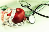 stock photo of measurement  - red apple wrapped with tape measure near scale with stethoscope - JPG