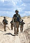 picture of battlefield  - Squad of soldiers patrolling across the desert - JPG