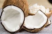 stock photo of coco  - A open coconut with grated coconut in the background - JPG