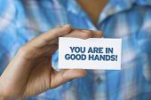 picture of slogan  - A person holding a white card with the words You are in Good hands - JPG