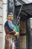 stock photo of bagpipes  - Bagpiper statue near the entrance to the building - JPG