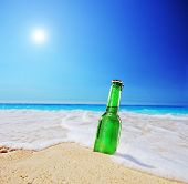 Beer bottle on a sandy beach with clear sky and wave, shot with a tilt and shift lens