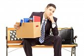 Disappointed redundant young man in a suit sitting on a bench with a box of belongings isolated on w