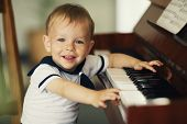 stock photo of preschool  - little funny boy plays piano - JPG