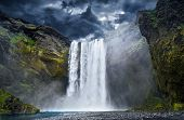 picture of chute  - Stormy sky over roaring waterfall and lush cliffs in Iceland - JPG