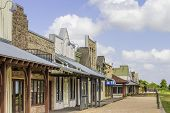 picture of west village  - A row of old western rural shops with a bright blue sky in the background - JPG
