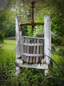 image of wine-press  - Antique wooden wine press left in garden surrounded by flowers - JPG