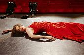 Sensuous young woman in red gown lying on stage floor