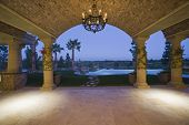 stock photo of hacienda  - Scenic view of landscape and pool through arched structure - JPG