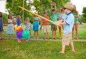 image of pinata  - Boy swings a stick at a pinata at kid - JPG