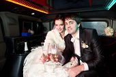 stock photo of limousine  - Bride and groom in wedding limousine with champagne - JPG