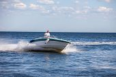 foto of outboard  - Man driving a fast boat  - JPG
