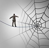 pic of trap  - Businessman trap business concept with a tightrope walker walking on a wire leading to a giant spider web as a metaphor for adversity and deception of being lured to a financial ambush or recruiting new career candidates - JPG