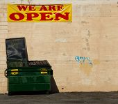 stock photo of dumpster  - large green dumpster lid open with a pink wall behind it and a WE ARE 0PEN sign above it - JPG