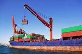 stock photo of international trade  - Cargo container ship under loading in a seaport - JPG