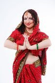 pic of namaskar  - european brunette girl in red indian saree with her hands in namaste on gray background in studio - JPG