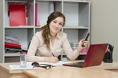 stock photo of boredom  - Young girl working at the desk in the office